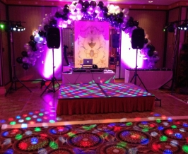 Indoor party stage setup with uplights, balloons, speakers, gobo projector and dance floor lighting.