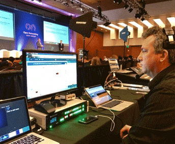 AV technician sitting behind computer display at technology conference in San Francisco.