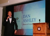 Dan Ashley speaks with microphone next to podium on stage with monitor display behind him at Diablo Country Club fundraiser.