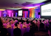 Indoor conference room AV stage setup with display screens, stage lighting and table decor at Gala Fundraiser at Riviera Hotel in Palm Springs.