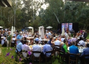 Guests at tables at large outdoor garden party fundraiser in Rancho Santa Fe with outdoor stage, sound, and AV setup.