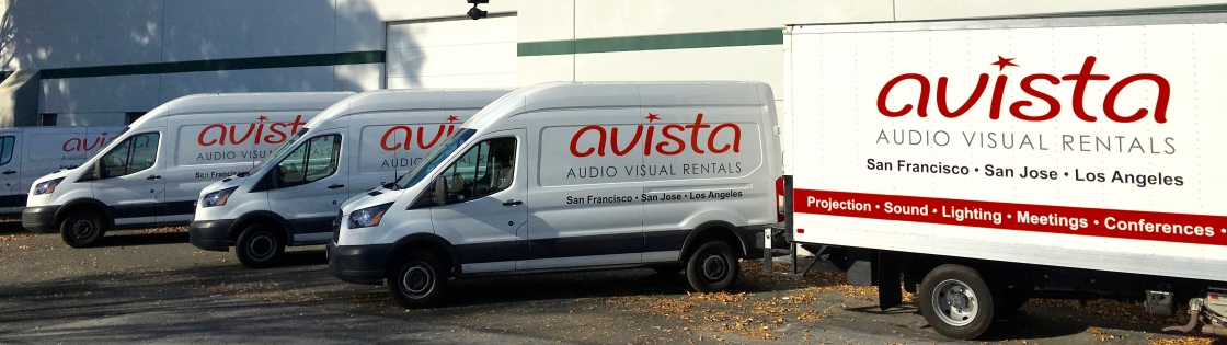 Row of Avista AV Rentals vans and truck in parking lot.