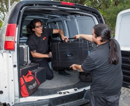 Techs unloading karaoke gear from van.