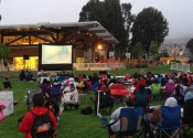 Crowd watches movie on inflatable screen on outdoor lawn by lodge.