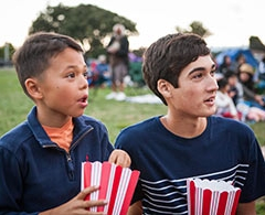 Two boys with popcorn watch outdoor movie.