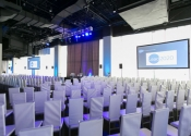 all white room setup for corporate meeting with projection screens.