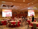 Ballroom set for lunch with two large screens displaying images.