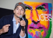 Ashton Kutcher speaks with microphone at indoor Steve Jobs movie premiere in San Francisco with movie poster display in background.
