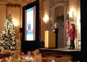 Woman speaks at podium on stage by large projection screen display and Christmas tree at Sheraton Palace Hotel Association Conference.