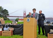 Man speaks at podium at outdoor press conference on lawn with table booth setup, police and Golden Gate Bridge behind.