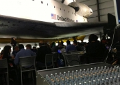 Sound and lighting control panel setup behind guests sitting in front of large plane at California Science Center dinner.
