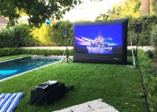 An inflatable outdoor movie screen setup on grass in a backyard in Pasadena.