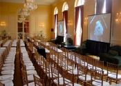 Large indoor business meeting conference AV setup with projection screens, sound and display setup with glass podium.