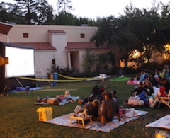 Crowds on picnic blankets watch outdoor movie on inflatable screen in large backyard.