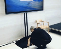 technician placing cover on TV display stand setup for corporate meeting.