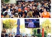 Large crowd and elevated TV monitor display at outdoor World Series event at San Francisco restaurant.