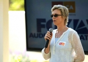 Jane Lynch speaks with microphone at Santa Barbara Garden Party Fundraiser.