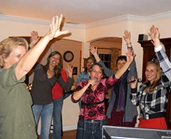 Group of party people doing karaoke in a living room.
