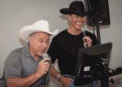 karaoke machine rental being used by two men in cowboy hats.
