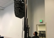 Speaker line array being hoisted into air by technician.