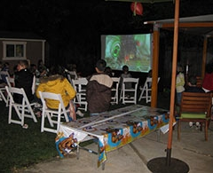 Family and friends watch outdoor movie on inflatable screen at night in backyard.
