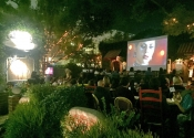 Diners enjoying movie playing at outsid restaurant