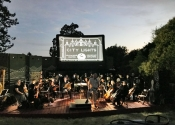orchestra playing outdoors in front of giant inflatable movie screen showing Charlie Chaplin movie.