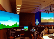 Indoor AV setup with screens, computer monitors, control systems, sound, display and stage lighting in Mission Bay Conference Center, San Francisco.