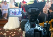 video camera viewfinder showing outdoor wedding ceremony.