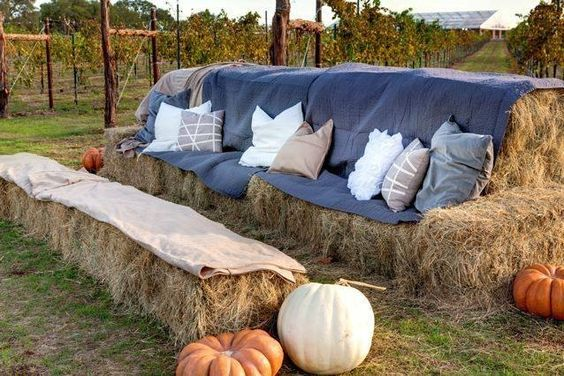 Haystacks set up as large couch with blanket cover, pillows and pumpkins next to outdoor vineyard.
