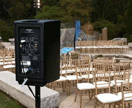 Black sound system speaker set up at outdoor event.