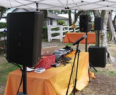 iPlay sound system tent booth display setup with microphones, speakers, subwoofers, laptop and mixer.