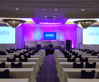 ballroom set for corporate conference with projection screens and tv displays