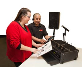 Tech support shows iPlay sound system to woman, including speakers, mixer and iPhone.