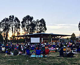 large audience waiting for outdoor movie to begin in south san francisco.