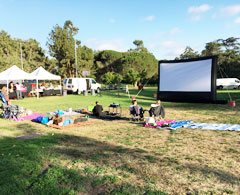 an inflatable movie screen setup in a park in los angeles at sunset.