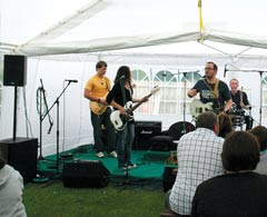 Band plays on stage under tent with iPlay sound system setup.